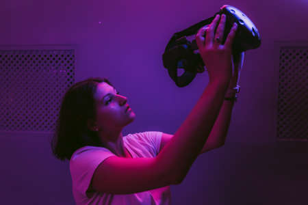 The girl connects to augmented reality. New technologies in games, movies, entertainment. Neon room.