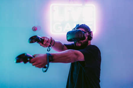 VR E-Sports. The guy is playing an online shooter in the game neon room. Standard-Bild - 151003994