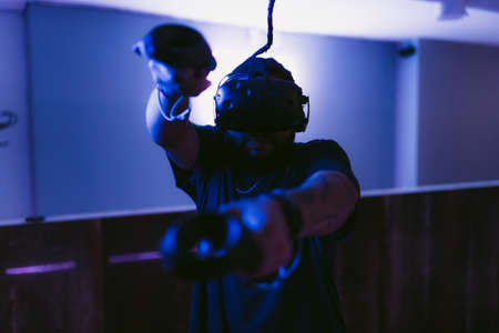 Man in a cyber helmet. New VR games in the neon room. 免版税图像