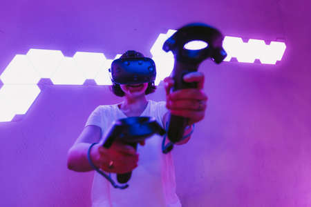 Girl playing games in VR glasses. Neon purple room. Cyberpunk games.