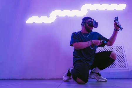 Virtual reality in a neon purple room. Man in VR glasses. Standard-Bild - 151385743