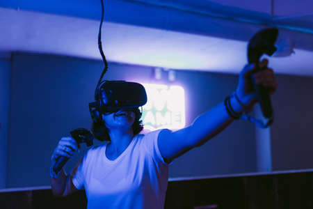 The girl gets new impressions of virtual reality. Neon gaming room.