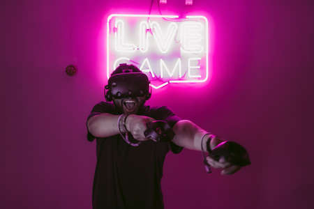 Extreme in virtual reality. Man playing games through VR helmet.