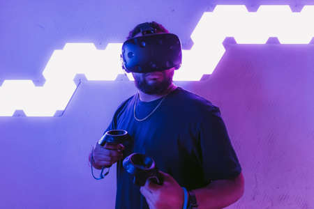 Virtual reality in a neon purple room. Man in VR glasses. Standard-Bild - 151385550