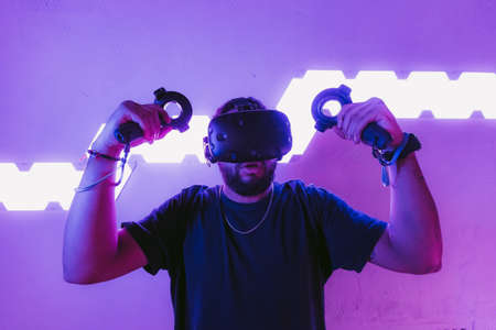 Virtual reality in a neon purple room. Man in VR glasses.