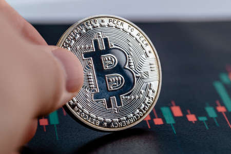 Close-up photo of crypto coin in hands. Bitcoin economy. 免版税图像