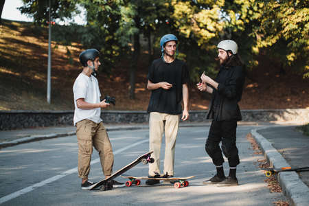 Three guys talk about skateboarding. 免版税图像