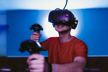 VR E-Sports. The guy is playing an online shooter in the game neon room.