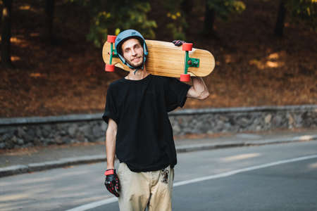 Portrait of a guy with a longboard on his shoulder. Skateboarding in summer.