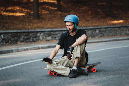 The guy is sitting on a logboard. Rest after skateboarding.