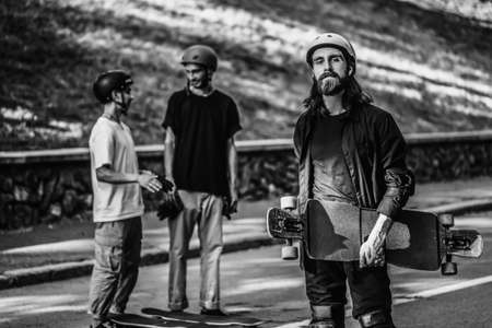 A group of guys ride longboards. Black and white portrait of a skateboarder.