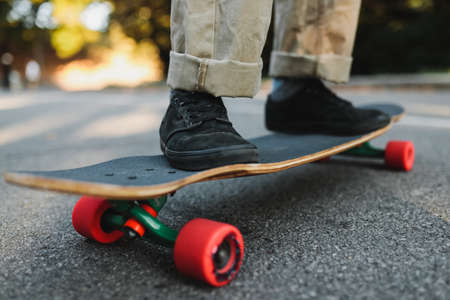 Longboard with red wheels on the asphalt.