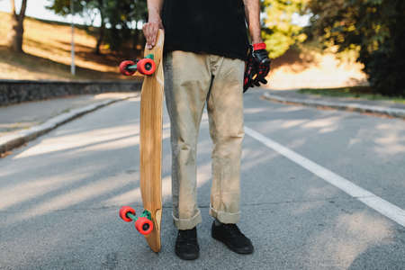 The guy is holding a board with red wheels. Skateboarding in the eternal city. 免版税图像