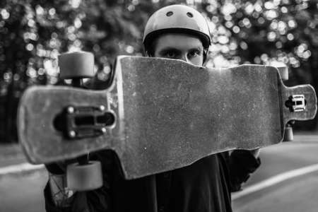 The guy is holding a longboard. Black and white portrait of an athlete.