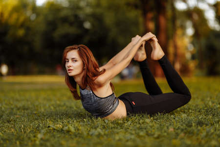 Girl in a bow pose. Woman doing yoga in the park.