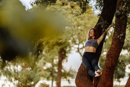 Girl in the park on a tree. Satisfied girl