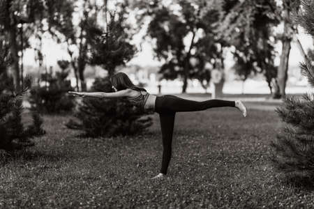 The girl performs body balancing. Yoga and fitness.