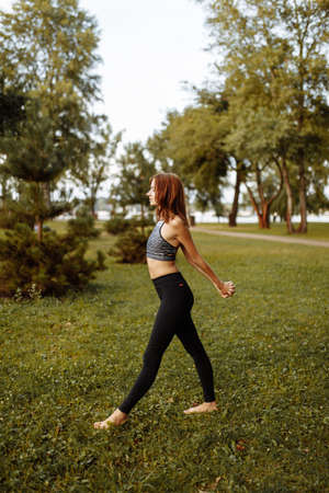 Beautiful girl doing a warm-up before yoga in the park.