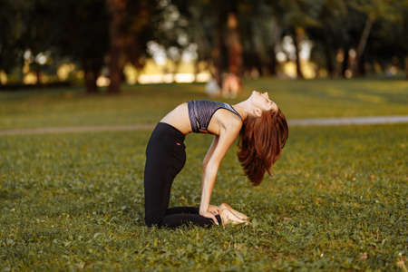 Fitness and yoga in nature. The girl is warming up and medinating in the park.