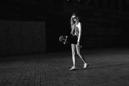 Contrasting black and white portrait of a woman with a skate in his hands. Standard-Bild