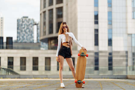 Growth portrait of a woman and a longboard.