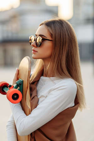 Woman in glasses with a skate in her hands. Longboarding around the city.
