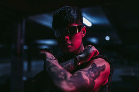 Man in the night city. Portrait of a man with Asian appearance in a neon city.