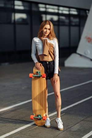 Growth portrait of a beautiful blonde with a skateboard. Lifestyle in the city