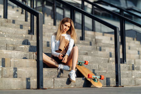 Beautiful blonde is resting after skateboarding.