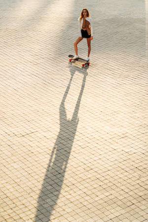 A woman skates in the evening city.