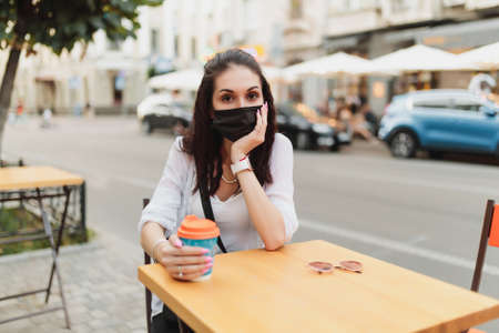 Young woman sitting on the street in a mask with a cup of coffee. Standard-Bild