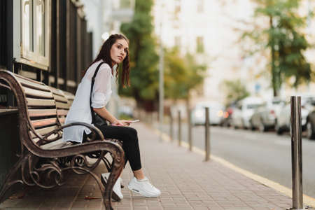 Young beautiful woman waiting for the bus at the stop. Standard-Bild