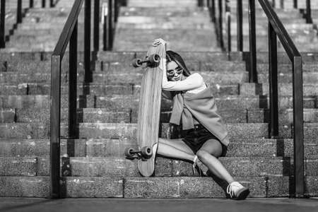 Woman with a skate sitting on the stairs.