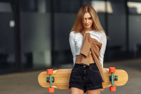 Breast portrait of a beautiful blonde with a skateboard. Lifestyle in the city