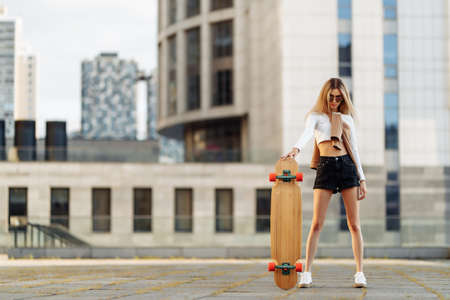 Young woman rides a longboard around the city. Standard-Bild