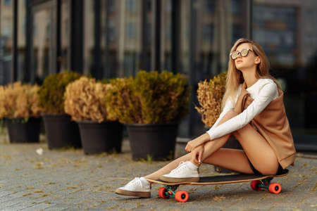 Beautiful girl with glasses sitting on a skateboard.