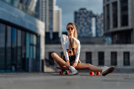 Sexy girl sitting on a skateboard under the sunset.