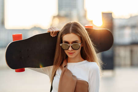 Portrait of a woman with a skate on his shoulder. Beautiful summer evening in the city. Standard-Bild