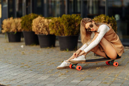 Woman with glasses sitting on a skateboard. Lifestyle in the city.