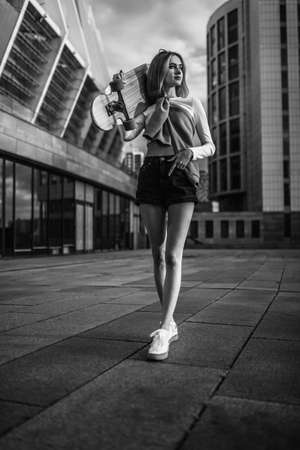 Woman on a skateboard in the city. Beautiful contrasting black and white photo of a woman riding around the city.