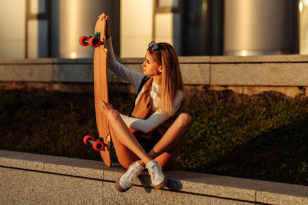 Lifestyle portrait of young woman with longboard. Standard-Bild