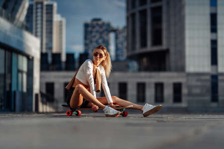 Sexy blonde with glasses sitting on a skateboard.