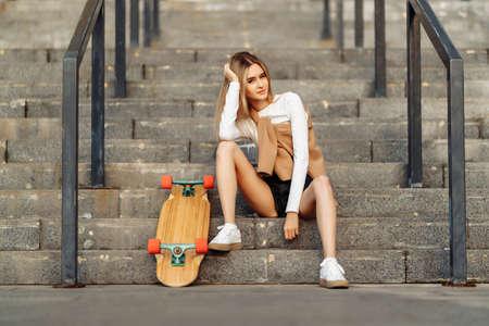 Beautiful woman skates around the city. Lifestyle and summer vacation. Standard-Bild