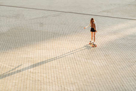Young woman rides a skateboard under the sunset.