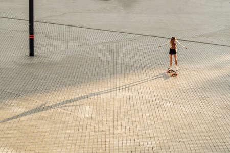 Longboarding in the evening city. Woman on a skateboard.