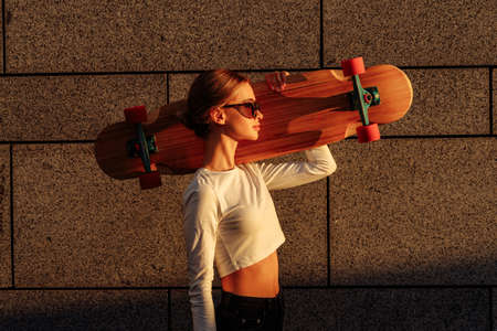 A beautiful ray falls on a woman with a skateboard.