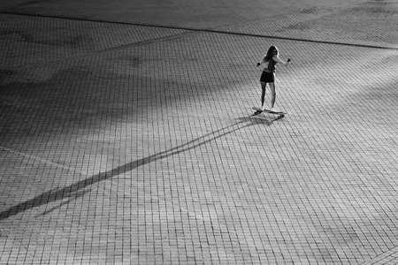 Portrait of a full-length girl on a skateboard under the sunset. Standard-Bild