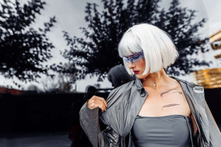 Stylish blonde in futuristic clothes and glasses on a mirror background.