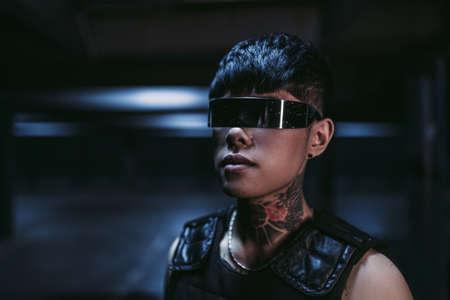Cyberpunk style. Tattooed guy in one city. Cyber glasses. 免版税图像