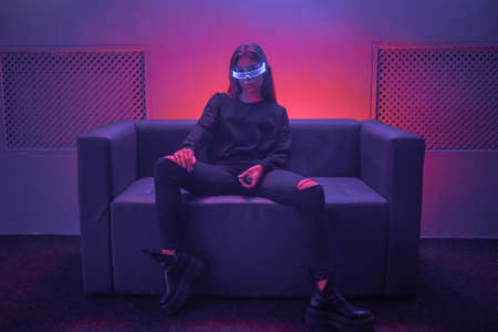 Cyberpunk woman sitting on sofa with neon glasses. The photo has the effect of shush, grain.